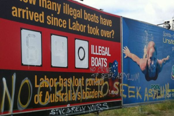 The figures were whited out and turned to zero with 'no crime to seek asylum' written on the Liberal Party billboard. ABC: Barry Duxton